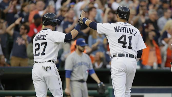 Detroit Tigers' Andrew Romine and Victor Martinez high-five after scoring against the Toronto Blue Jays on a single by Nick Castellanos during the fourth inning of a baseball game Friday, July 3, 2015, in Detroit. (AP Photo/Duane Burleson)
