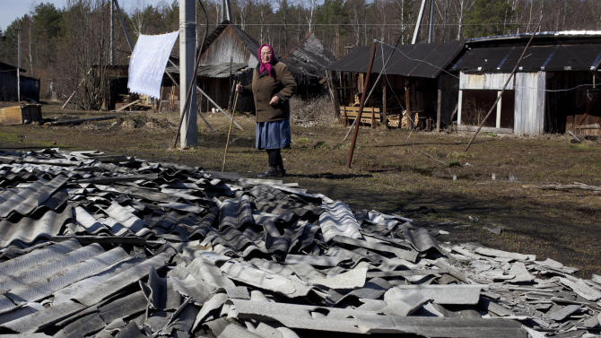 An elderly woman looks at roof debris at a site of a fire of a psychiatric hospital Friday morning, April 26, 2013. At least 38 people died in a fire in a psychiatric hospital outside Moscow late Thursday night. Police said the fire, which broke out at about 2 a.m. local time (6 p.m. Eastern, 2200 GMT) in the one-story hospital in the Ramenskoye settlement, was caused by a short circuit. (AP Photo/Pavel Sergeyev)