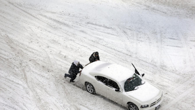 Two men help push a car down a snow-covered street Thursday, Feb. 21, 2013, in St. Louis. Blinding snow bombarded much of the nation's midsection Thursday, causing whiteout conditions, making major roadways all but impassable and shutting down schools and state legislatures. (AP Photo/Jeff Roberson)