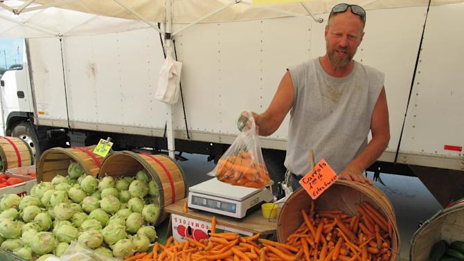 In this July 12, 2012, photo, David Witte, a farmer in West Bend, Wis., packages carrots for sale at a farmers market in nearby West Allis, Wis. Farmers in the Midwest are struggling after a searing heat wave and prolonged drought took a toll on their summer harvests, and farmers say it's even more important now for customers to support local growers by continuing to shop at farmers markets. (AP Photo/Dinesh Ramde)