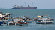 Philippine fishing boats are anchored near a foreign cargo vessel facing the South China sea at the port of Santa Cruz town, Zambales province, north of Manila, on May 10. For years Filipino and Chinese fishermen peacefully shared the rich harvests around a tiny South China Sea shoal, but today threats, harassment and fear have replaced ocean comradery