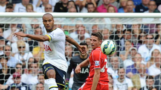 Younes Kaboul (left) clears the ball past Liverpool's Joe Allen (R) during a Premier League game at White Hart Lane in London on August 31, 2014