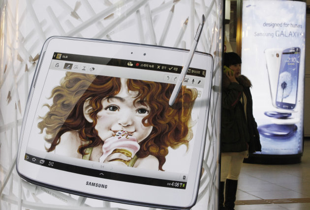 <p>               A woman uses her smartphone between a billboard of Samsung Electronics' Galaxy S III and Galaxy Note 10.1, left, at a subway station in Seoul, South Korea, Friday, Jan. 25, 2013. Samsung Electronics Co. said quarterly profit soared 76 percent, boosted by the popularity of its Galaxy smartphones, which outsold the iPhone for a fourth straight quarter. But the company said Friday it expects earnings to decline during the current quarter because of seasonally low demand for consumer electronics. (AP Photo/Ahn Young-joon)