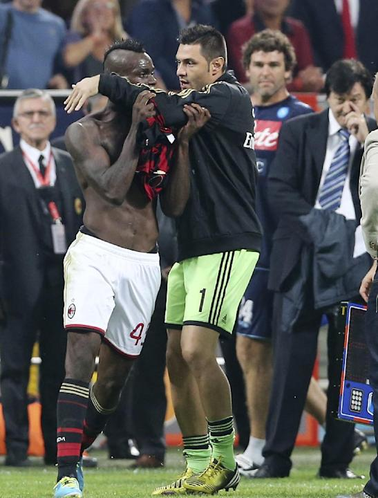 AC Milan forward Mario Balotelli, left, is restrained by teammate Marco Amelia after receiving a red card at the end of the Serie A soccer match between AC Milan and Napoli at the San Siro stadium in