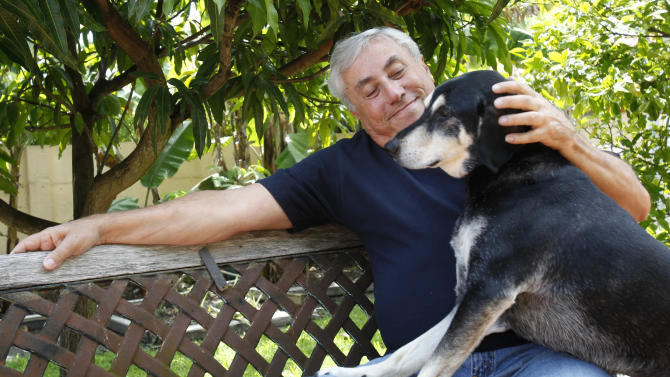 In this photo taken Tuesday, May 29, 2012, Leon Rozio pets his dog Peggy at his home in Miami. Rozio, 68, a former jewelry salesman, retired after he was robbed of more than $160,000 in 2008 in Boca Raton, Fla. He was waiting in his car while his partner was in the jewelry store when at least three men busted out the windows. One reached in and grabbed a small duffel bag of jewelry. Rozio fired his pistol at their car, which he said tried to run him over. One of the men was fatally wounded, but Rozio wasn't charged because the shooting was deemed self-defense. He left the business at his family's urging. (AP Photo/Alan Diaz)