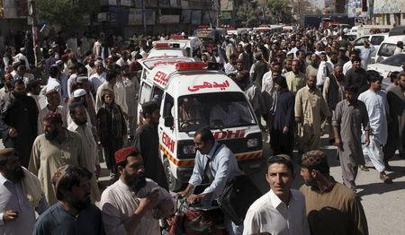 People escort ambulances, carrying victims of an attack on buses, to the hospital in Quetta