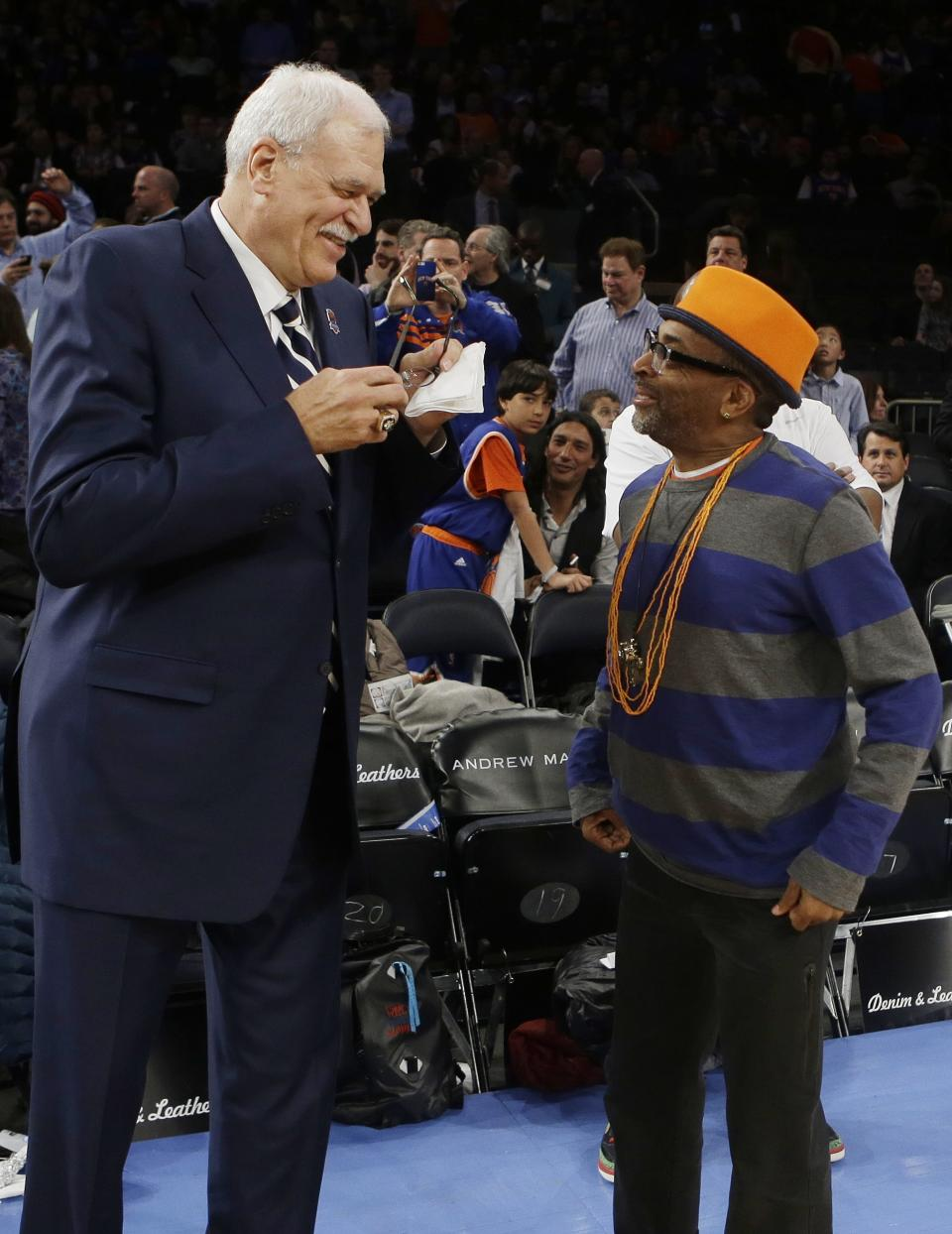 Former NBA coach Phil Jackson, left, and director Spike Lee, right, talk before a ceremony to honor the 1972-73 Championship New York Knicks team during the first half of an NBA basketball game between the Knicks and the Milwaukee Bucks, Friday, April 5, 2013, in New York. (AP Photo/Frank Franklin II)