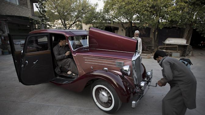 In this photo taken April 14, 2015, a man jump starts a six cylinder Wolseley 1936 model car, in Islamabad, Pakistan. For an elite but passionate group of vintage car collectors in Pakistan, restoring antique rides is like traveling back in time and money seems to be no obstacle when the prize is a Lincoln convertible that belonged to an Afghan king or a Rolls-Royce once used by India's last viceroy. (AP Photo/B.K. Bangash)