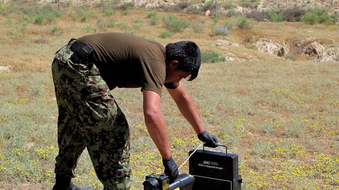 In this Tuesday, June 11, 2013 photo, Hayatullah places a scanner on an IED (improvised explosive device) during a defusing training exercise on the outskirts of Kabul, Afghanistan, Tuesday, June 11, 2013. A few years ago, there were almost no Afghan bomb disposal experts. Now, there are 369 _ and the international coalition is rushing to train hundreds more before the exit of most coalition forces by the end of next year. (AP Photo/Kay Johnson)