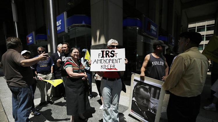 Polly Beckham, of Ambler, Pa., holds a sign during a tea party rally protesting extra IRS scrutiny of their groups, Tuesday, May 21, 2013, in Philadelphia. Tea party groups and other groups are urging activists across the country to demonstrate at their local Internal Revenue Service offices. (AP Photo/Matt Slocum)