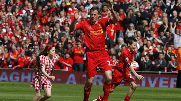 Liverpool's Jamie Carragher runs onto the pitch with his children
