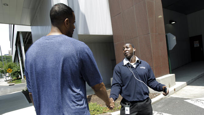 In this Tuesday, June 19, 2012, photo, former NBA basketball star Jayson Williams, left, greets Lorenzo Holloway, 27, who was walking on the street and recognized him in Weehawken, N.J. Williams, who was recently released from prison, is trying to plug himself back into society. (AP Photo/Julio Cortez)
