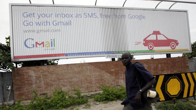 In this photo taken, Monday, Sept.17, 2012. An unidentified man walk past a Google advert in Lagos, Nigeria. With all its cutting-edge technology, Google Inc. has turned back to the text message in its efforts to break into Nigeria's booming economy. The search engine has started a service in Nigeria, as well as Ghana and Kenya, allowing mobile phone users to access emails through text messaging. That comes as the company's office in Lagos has begun working with small business owners in this nation of more than 160 million people. (AP Photo/Sunday Alamba)