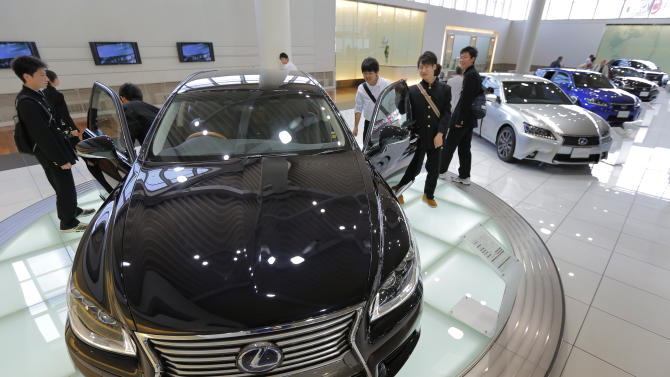 School boys look at Toyota Lexus LS600hL displayed at Toyota Motor Corp. showroom Toyota Mega Web in Tokyo Wednesday, May 8, 2013. Toyota's January-March profit more than doubled to 313.9 billion yen ($3.2 billion) as cost cuts and better sales worked with a weakening yen to add momentum to the automaker's comeback. (AP Photo/Itsuo Inouye)