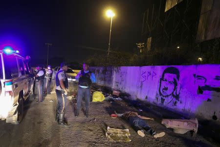 Police officers stand near the body of Anzoategui state policeman Mario Figueroa after he was shot dead in Barcelona, in the state of Anzoategui