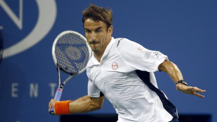 Tommy Robredo of Spain returns a shot to Nick Kyrgios of Australia during their men's singles match at the 2014 U.S. Open tennis tournament in New York