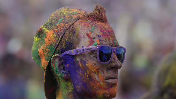 A reveler covered in colored corn starched looks on during the 2015 Festival of Colors, Holi Celebration at the Krishna Temple on Saturday, March 28, 2015, in Spanish Fork, Utah. (AP Photo/Rick Bowmer)