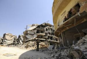 A Syrian army soldier loyal to Syria's President Bashar al-Assad chats with fellow fighters sitting on a balcony of a damaged building in Mleiha, which lies on the edge of the eastern Ghouta region near Damascus airport, after taking control of the area fr