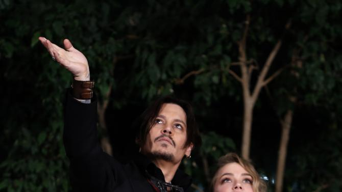 "Actors Johnny Depp and Amber Heard wave their hands as they leave the Japanese premiere of ""Mortdecai"" in Tokyo"