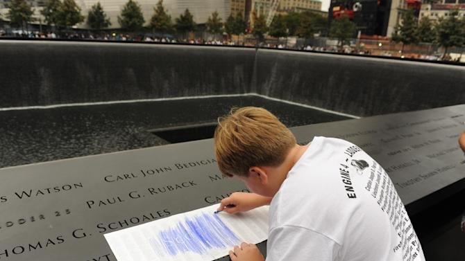 FILE - In this Sept. 11, 2011 file photo, August Larsen, 9, makes a crayon rubbing of the name of his father, Scott Larsen, engraved on the bronze parapet overlooking the south pool of at the National September 11 Memorial in New York on the 10th anniversary of the attacks on the World Trade Center. Scott Larsen, a firefighter at Ladder 15, never met his son, who was born just a few days after Scott's death in the terrorist attacks. The memorial, placed in the footprints of the twin towers, was designed with the rubbings in mind. (AP Photo/Aaron Showalter, Pool, File)
