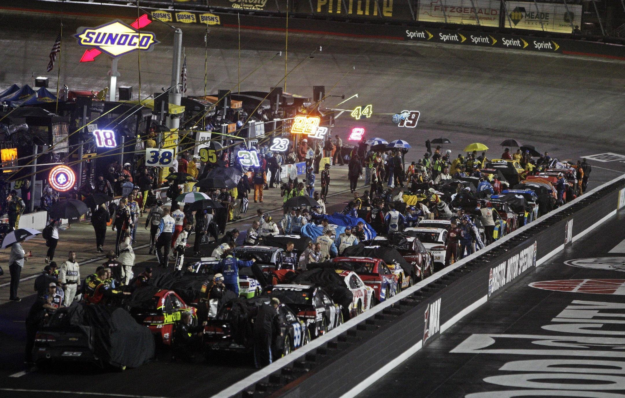 Crews cover cars under rain at Bristol. (AP)