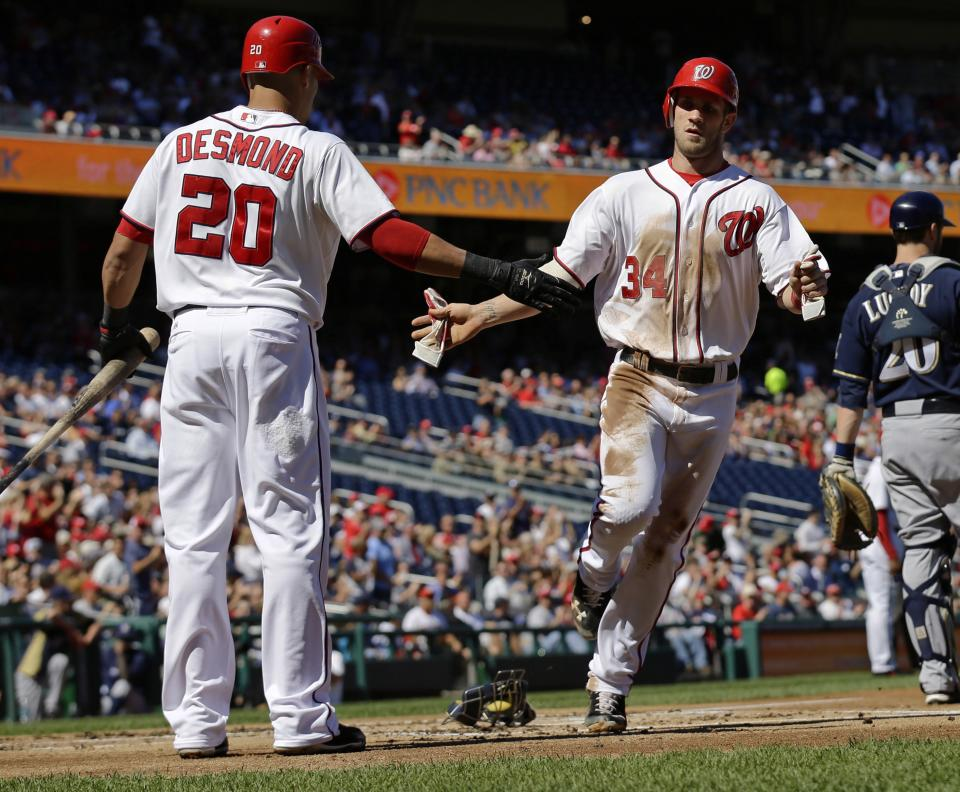 Washington Nationals' Bryce Harper, right, celebrates with Ian Desmond after he scored during the first inning of a baseball game against the Milwaukee Brewers at Nationals Park, Monday, Sept. 24, 2012, in Washington. (AP Photo/Alex Brandon)