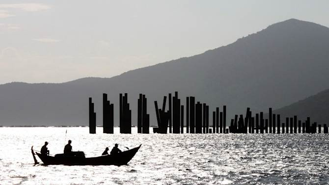 "In this photo taken April 10, 2011 photo, a boat passes by the abandoned Van Phong port in southern Vietnam. All that remains of a plan by Vietnam to build a major deep water port is 114 exposed pilings trailing into the South China Sea and a barge full of rusty machinery. Foreign investors stayed away from the $3.6 billion project and the indebted state-owned company overseeing it bungled the job. Earlier this month, Sept., 2012, the government accused the company of ""financial incompetence"" and suspended the project. The prospects for ever reviving it are dim. (AP Photo/Tuoi Tre Newspaper, Van Ky) VIETNAM OUT"