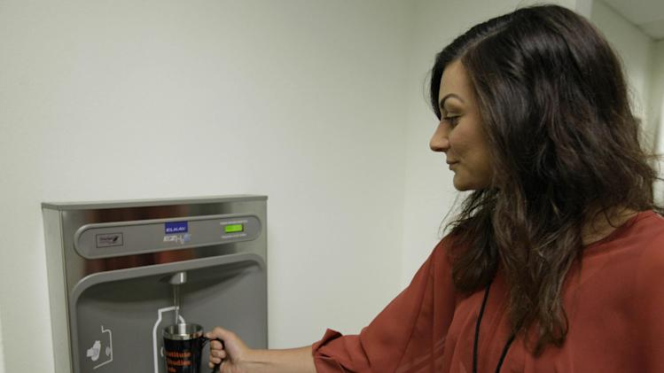 In this photo taken Thursday, July 5, 2012, Shauna Barbera uses a bottled water dispenser at the California Institute of Integral Studies in San Francisco. The city that regulated Happy Meal toys and banned plastic grocery bags has a new target in its health-conscious, eco-friendly crosshairs: plastic water bottles. (AP Photo/Eric Risberg)