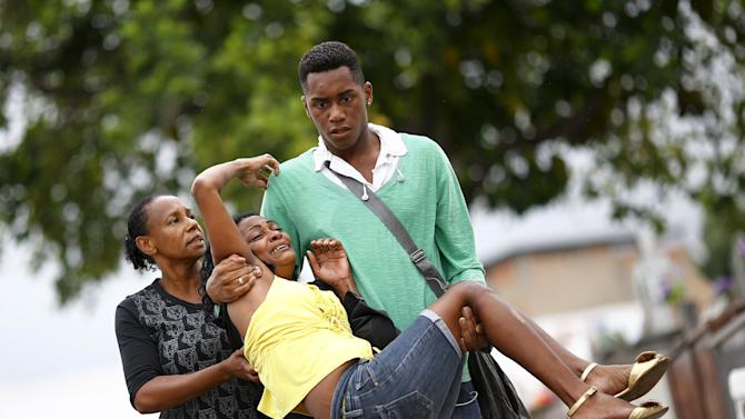Relatives of Wilton Esteves Domingos, one of five youths killed after being shot by police officers in Costa Barros neighborhood, react after his burial in Rio de Janeiro