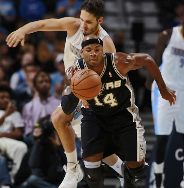 San Antonio Spurs forward Corey Maggette, front, pulls in a loose ball in front of Denver Nuggets guard Evan Fournier in the fourth quarter of the Nuggets' 98-94 victory in an NBA preseason basketball