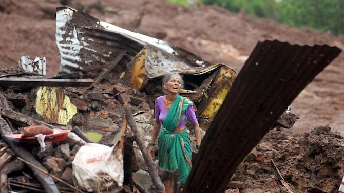 An elderly Indian woman cries as she searches for surviving family members in the debris of her home, destroyed by landslide in Malin village, in the western Indian state of Maharashtra, Wednesday, July 30, 2014. The landslide that hit early Wednesday morning killed more than a dozen and possibly trapping many more people under debris, officials said. With 70 homes buried and reports of another 158 hit by the landslide, rescuers anticipated more dead in the village, home to 704 people in the foothills of the Sahyadri Mountains. (AP Photo/Press Trust of India)
