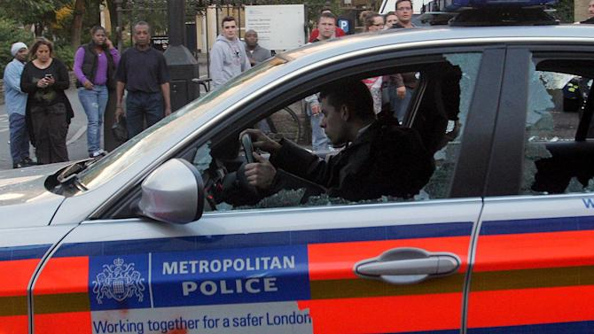A police officer drives a damaged vehicle during violent skirmishes between police and youths in Hackney, east London, Monday, Aug. 8, 2011. Violence and looting spread across some of London's most impoverished neighborhoods on Monday, with youths setting fire to shops and vehicles, during a third day of rioting in the city that will host next summer's Olympic Games. (AP Photo/PA, Lewis Whyld) UNITED KINGDOM OUT, NO SALES, NO ARCHIVE