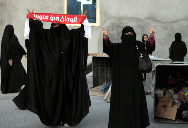 "Bahraini anti-government protesters gesture toward riot police who dispersed their planned march calling for the release of political prisoners in Bilad al-Qadeem, Bahrain, on Tuesday, Sept. 25, 2012. Police chased protesters with tear gas and stun grenades as they arrived for the march, preventing it from starting. The banner reads: ""The nation is in our hearts."" (AP Photo/Hasan Jamali)"