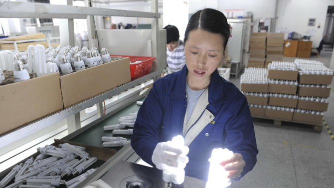 In this Nov. 9, 2011 photo, a worker tests compact fluorescent lamps (CFL) at a factory in Hangzhou in eastern China's Zhejiang province. China's manufacturing sector was boosted by strong holiday season demand for food, beverages and other consumer products in January, though export demand and other indicators remained weak, according to surveys released Wednesday, Feb. 1, 2012. (AP Photo)  CHINA OUT