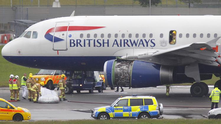 Emergency services attend a British Airways passenger plane after it had to make an emergency landing at Heathrow airport. early Friday May 24, 2013. Both runways at Heathrow airport were briefly closed after the British Airways plane made an emergency landing, and Heathrow said that all passengers and crew were safely evacuated from the plane following the incident. Footage broadcast on British television shows the plane in the air with smoke streaming from one engine (not the engine shown in this photo). (AP Photo/Steve Parsons, PA) UNITED KINGDOM OUT - NO SALES - NO ARCHIVES