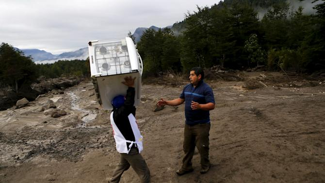 A resident carries a stove through an area damaged by lahar from Calbuco Volcano at Correntoso near Chamiza