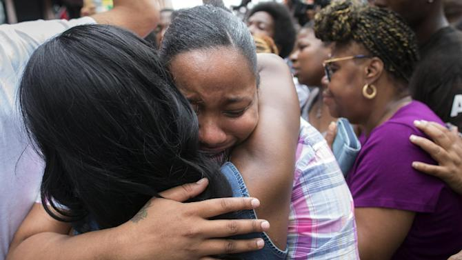 Emerald Garner, daughter of Eric Garner, mourns at the site of her father's death on a march following a service held in his name at the Mount Sinai Center for Community Enrichment, Saturday, July 19, 2014, in the Staten Island borough of New York. The wife of a man who died after a police officer used an apparent chokehold to bring him to the ground during an arrest burst into tears Saturday at a Harlem rally in his honor. Eric was confronted by police trying to arrest him on suspicion of selling untaxed, loose cigarettes on a Staten Island sidewalk, authorities said. (AP Photo/John Minchillo)