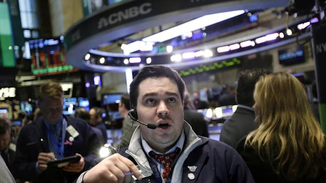 """A trader works on the floor at the New York Stock Exchange in New York, Wednesday, Jan. 2, 2013. The """"fiscal cliff"""" compromise, for all its chaos and controversy, was enough to send the stock market shooting higher Wednesday, the first trading day of the new year. (AP Photo/Seth Wenig)"""