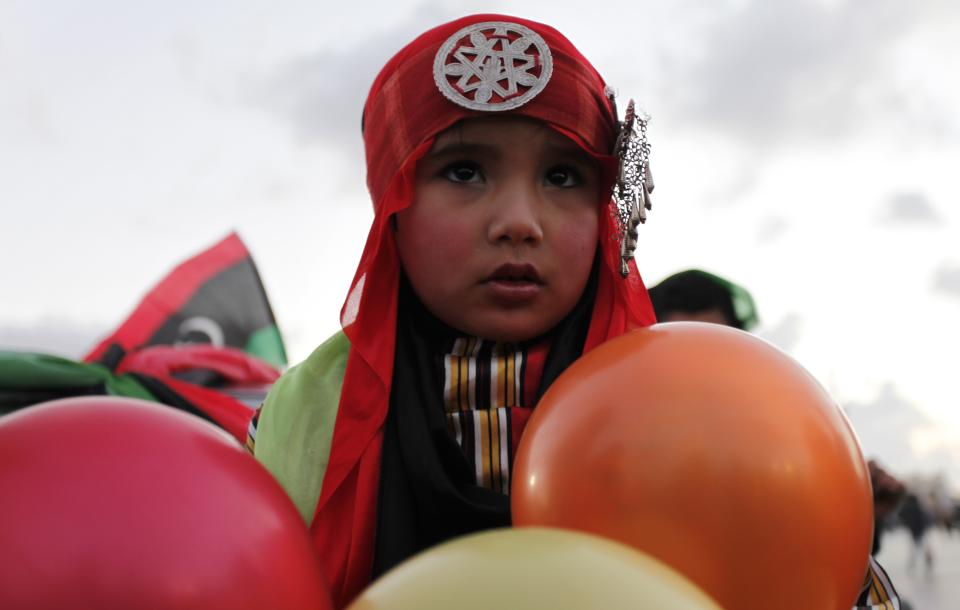 Libyan girl, wears traditional Libyan clothes, pose at Tahrir Square, during the second anniversary of the uprising that toppled longtime dictator Moammar Gadhafi in Benghazi, Libya, Sunday, Feb, 17, 2013.  (AP Photo/Mohammad Hannon)