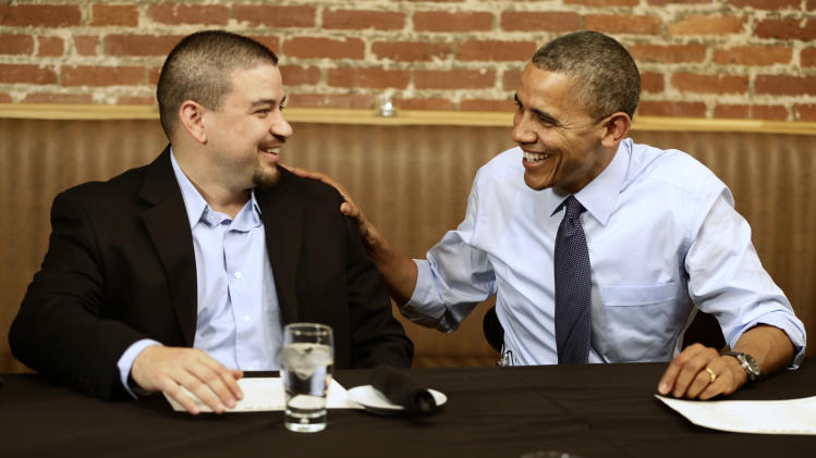 """President Barack Obama meets with Mario Orosa, left, of North Canton, Ohio, and other winners of the """"Dinner With Barack"""" campaign fundraising contest at Smith Commons Dining Room and Public House in Washington, on Friday, Oct. 12, 2012. (AP Photo/Jacquelyn Martin)"""