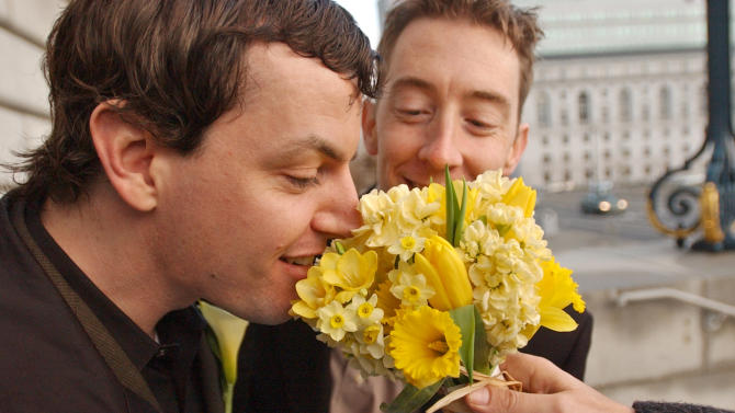 In this file photo from Tuesday, Feb. 24, 2004, Aaron Carruthers, left, and Keith Haberstuck, of Sacramento, Calif., smell flowers prior to their planned wedding at City Hall in San Francisco. The U.S. Supreme Court decided Friday, Dec. 7, 2012, to hear the appeal of a ruling that struck down Proposition 8, the state's measure that banned same sex marriages. The highly anticipated decision by the court means same-sex marriages will not resume in California any time soon. The justices likely will not issue a ruling until spring of next year. A federal appeals court ruled in February that Proposition 8's ban on same-sex marriage was unconstitutional. But the court delayed implementing the order until same-sex marriage opponents proponents could ask the U.S. Supreme Court to review the ruling. (AP Photo/Ben Margot)