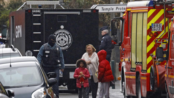 "A woman and children are escorted by a police officer near a building where the chief suspect in an al-Qaida-linked killing spree is holed up in an apartment in Toulouse, France Thursday March 22, 2012. Mohamed Merah France's chief suspect in the shooting of three Jewish schoolchildren, a rabbi, and three French paratroopers in three separate incidents wants to ""die with weapons in his hands,"" the interior minister said Thursday, as a standoff between the gunman and hundreds of police entered a second day.(AP Photo/Remy de la Mauviniere)"