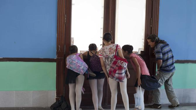 """In this April 3, 2013 photo, ballet students and a student's father watch a class through a window at the National School of Ballet in Havana, Cuba. The school was founded seven decades ago by famed prima ballerina assoluta Alicia Alonso, now age 92, who is probably the most recognized person in Cuba not named """"Castro."""" (AP Photo/Ramon Espinosa)"""