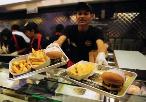 A Pakistani Fatburger employee serves burgers to a customer in Karachi on January 10, 2013. The UN's food agency says obesity and poor nutrition weigh heavily on the global economy and tells governments that investing in food health would bring big economic as well as social returns