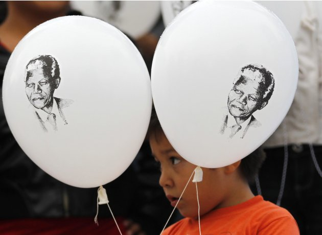 A child holds up balloons with images of former South African President Nelson Mandela in Mexico City. Supporters around the world wished the anti-apartheid leader happy birthday as he celebrated his