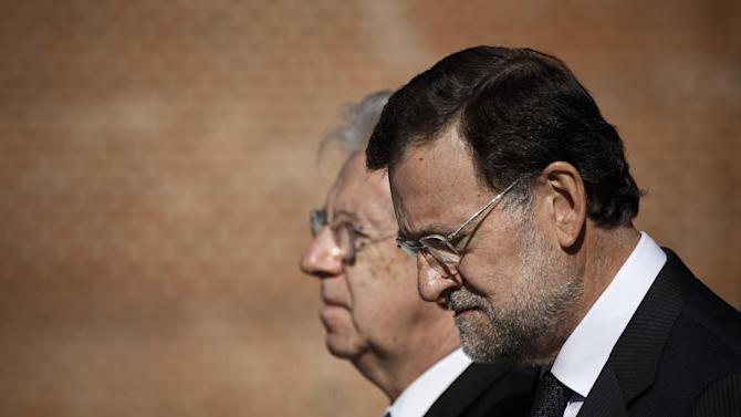 Spain's Prime Minister Mariano Rajoy, right, and Italian Premier Mario Monti listen to national anthems during a welcome ceremony before a meeting at the Moncloa Palace, in Madrid, Monday, Oct. 29, 2012. (AP Photo/Daniel Ochoa de Olza)