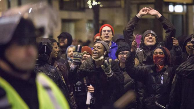 People yell at police during a demonstration against a grand jury's decision in the Ferguson shooting of Michael Brown in Seattle