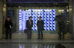 Pedestrians taking shelter from snow stand in front of an electronic board showing stock prices outside a brokerage in Tokyo February 4, 2014. REUTERS/Yuya Shino