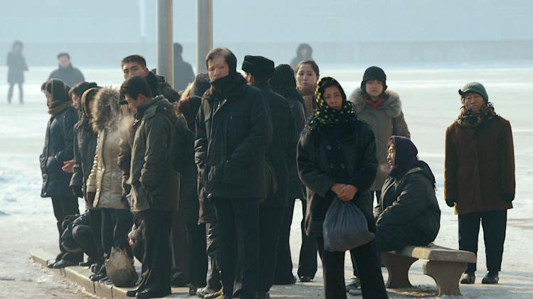 North Koreans wait for a bus in snow-covered Pyongyang, North Korea, Monday, Dec. 10, 2012. North Korea on Monday extended the launch period for a controversial long-range rocket by another week until Dec. 29, citing technical problems. (AP Photo/Kyodo News) JAPAN OUT, MANDATORY CREDIT, NO LICENSING IN CHINA, FRANCE, HONG KONG, JAPAN AND SOUTH KOREA