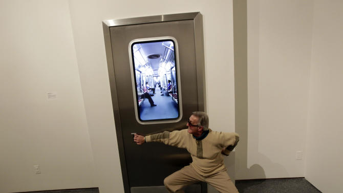 "In this Wednesday, Nov. 14, 2012 photo, museum patron Buz Burzelleri, of New Orleans, clowns for the camera as he pretends to open the door of the installation titled ""Subway,"" by artist Leadro Erlich, at the New Orleans Museum of Art, in New Orleans. The piece is part of ""Lifelike,"" a traveling exhibit at the New Orleans Museum of Art through Jan. 27. (AP Photo/Gerald Herbert)"